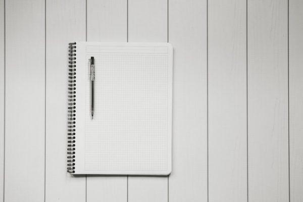 un carnet et un stylo sur un fond neutre